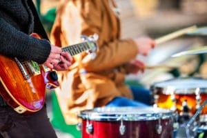 Festival music band. Hands playing on percussion instruments in park . Drums with sticks closeup. Sharpen is guitar and man hand.