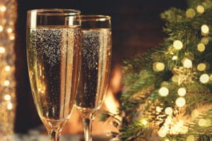 Two glasses with champagne on a wooden table near a Christmas tree during tours, things to do in Independence MO