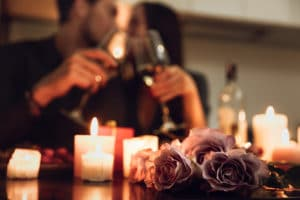 Couple toast with wine in front of candlelight dinner on a Romantic Bed and Breakfast getaway