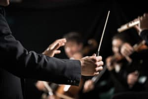 Conductor directing symphony orchestra with performers on background hands close-up at the Kansas City Symphony